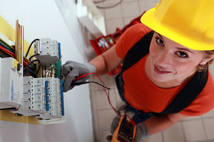 Female electrician checking circuitry