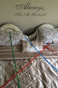 Geopathic stressors marked with rulers on the bed.